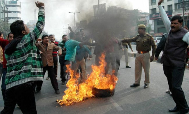 Activists of Bharatiya Janata Party (BJP) burn tyre to block a road during a protest in Guwahati...