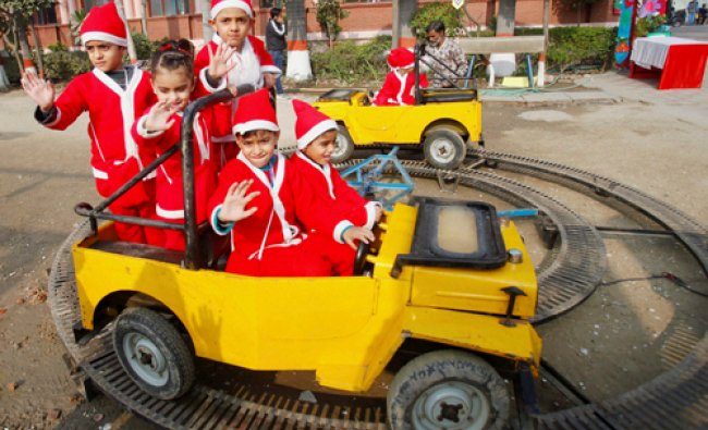 Students dressed up as Santa Claus enjoy a ride ahead of Christmas celebrations in New Delhi on...