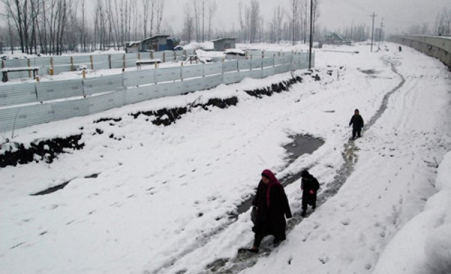 A family walks along the snow covered road at Anantnag District of South Kashmir on Tuesday...
