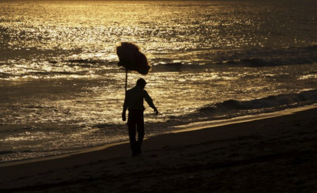 A vendor sells cotton candy ahead of Christmas at a beach in Puri, in the eastern Indian city of...