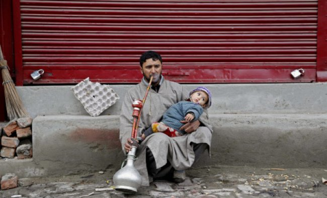 A Kashmiri man hold his baby as he smokes a hookah, or a hubble bubble, at a local market in...