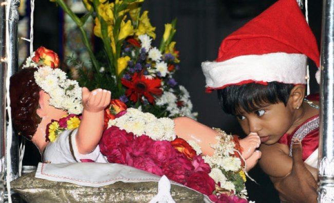 A child kisses the feet of an infant Jesus Christ after attending prayer on the occasion of...