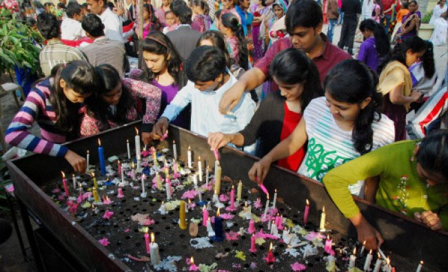 Devotees light candles outside a church on the occasion of Christmas Day in Surat on Wednesday.