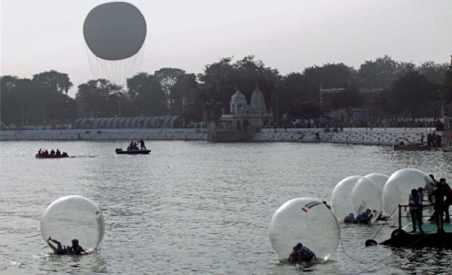 People enjoy in floating spheres as tourists throng Kankaria lake in Ahmedabad on Thursday during..