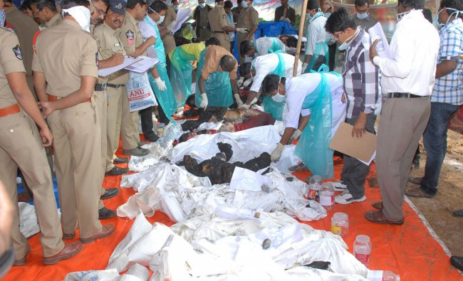 Security personnel and the medical team examine the dead bodies of the victims. The bodies are...