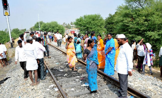 Onlookers at the spot where an AC coach of Bangalore-Nanded express caught fire near...