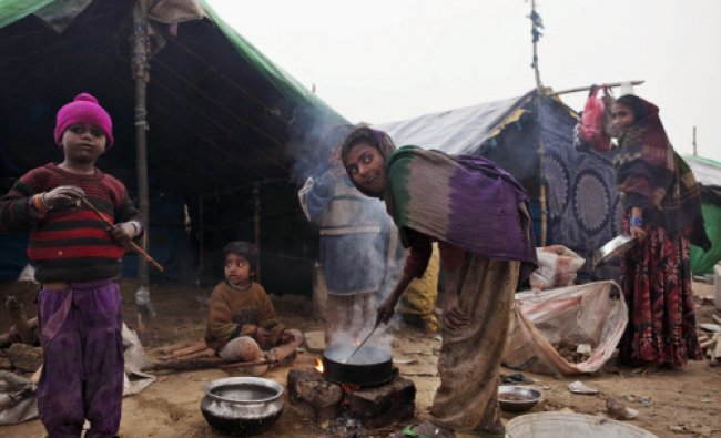 A young girl cooks a meal outside a makeshift tent as others do their daily chores, in New Delhi...