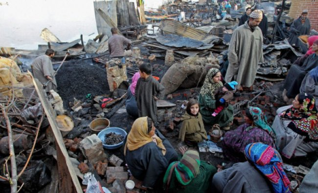 Survivors sift through debris where houses were gutted in a fire which broke out in Hazratbal...