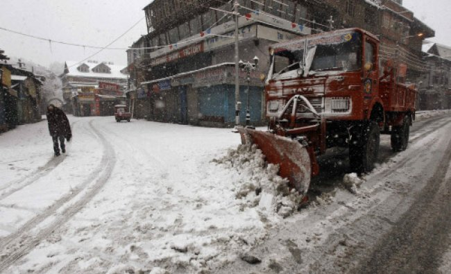 A snow-clearing machine removes snow from a road during snowfall on a cold winter morning in...