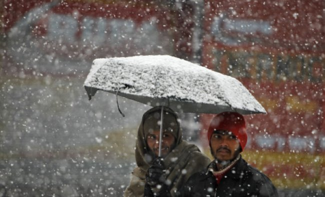 Men walk under an umbrella during snowfall on a cold winter morning in Srinagar December 31...