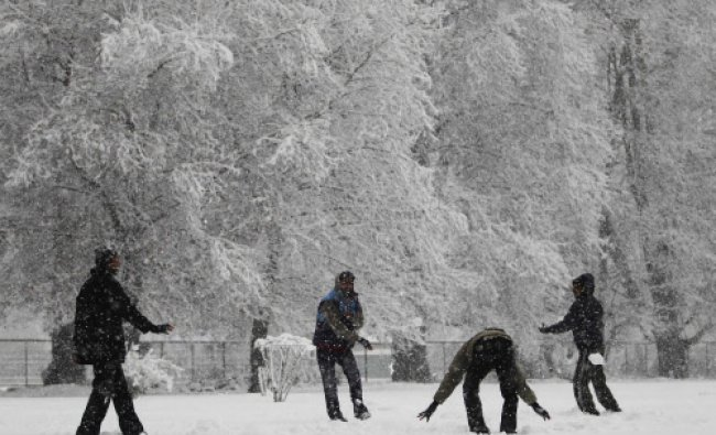 Tourists enjoy a snowball fight during snowfall on a cold winter morning in Srinagar December...