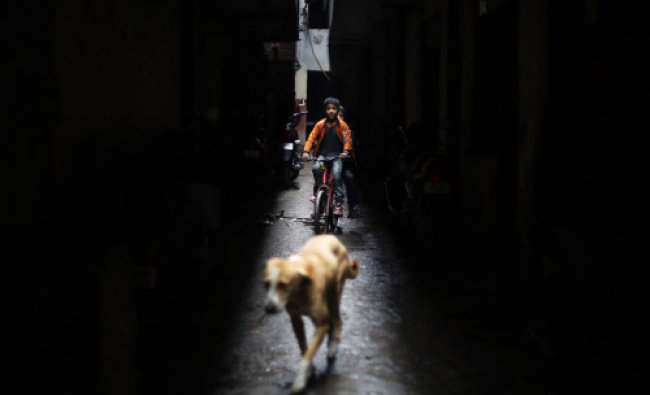 A boy rides a bicycle along a narrow alleyway in New Delhi, India, Tuesday, Dec. 31, 2013.