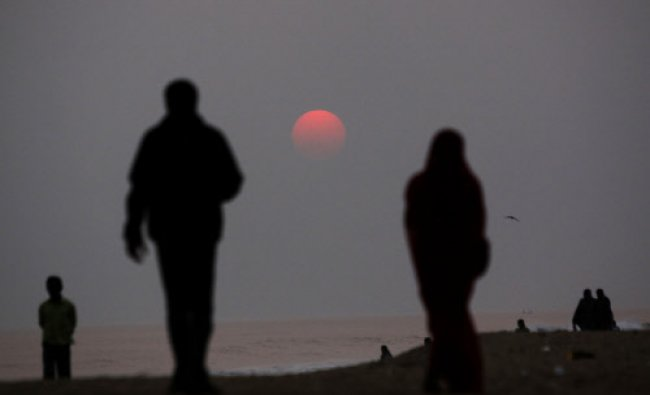 People walk on a beach as the sun sets on New Years Eve over the Bay of Bengal in Puri, India...