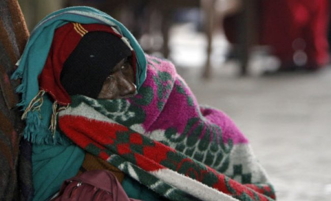 A stranded passenger sits wrapped in warm clothes as he waits for the Jammu-Srinagar highway to...
