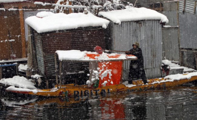 A Kashmiri boatman clears snow from the roof of a shikara, traditional gondola, in Srinagar...