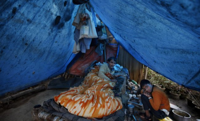 A man lies down under a quilt as his son sits beside him inside a makeshift tent on a cold day...
