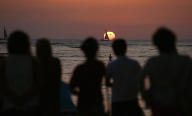 People watch a boat sail in front of the setting sun on New Year\'s Eve on Waikiki Beach...