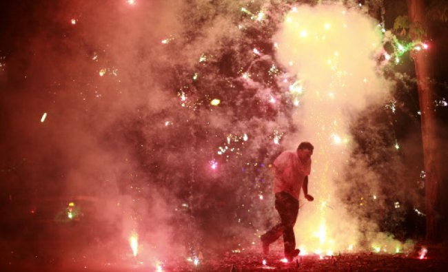 A man runs as firecrackers burst around him, on the street during the New Year celebrations ...