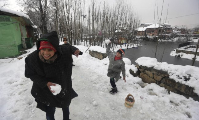 Kashmiri children throw snow at each other after fresh snow falls in Srinagar, India, Wednesday...