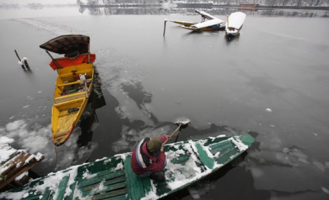 A Kashmiri man breaks the frozen surface of water at the Dal Lake in Srinagar, India, Wednesday...