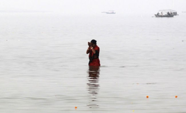 A devotee takes a holy dip at Sangam, the confluence of the Ganges, Yamuna and Saraswati rivers...