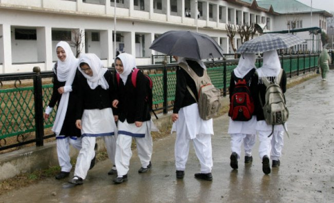 School girls walks to attend their classes amid rains on the day...