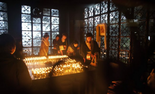Exile Tibetans in traditional dresses light butter lamps next to a portrait...
