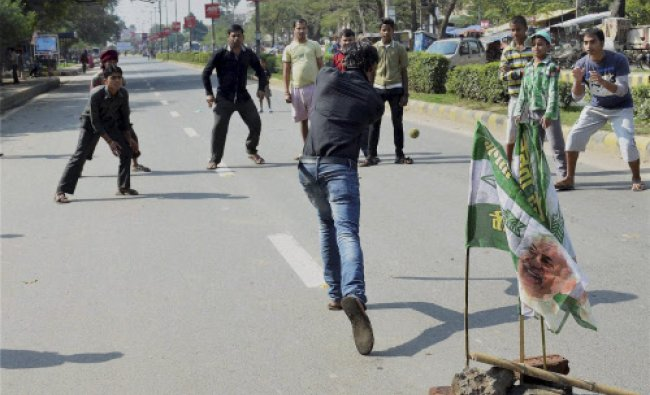 People play cricket on a deserted road during Bihar bandh organised by JD(U)...