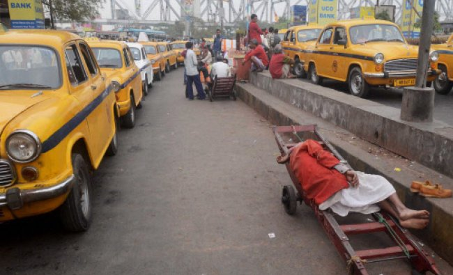 A railway porter takes a nap at Howarh Rail Station in Kolkata on Sunday as trains movement...