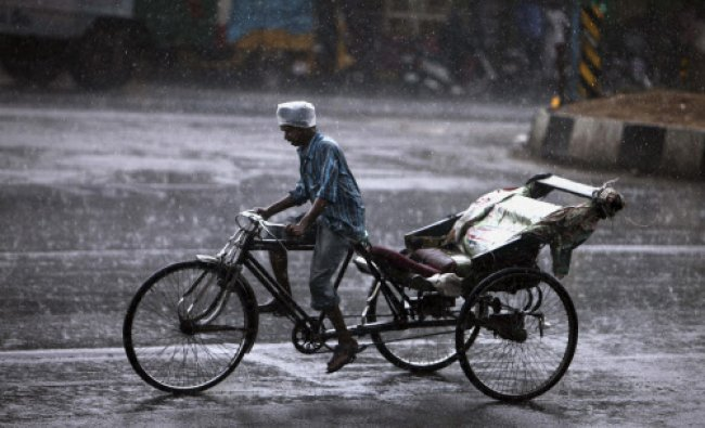 An Indian rickshaw puller protects his head with a plastic cover from rain in Hyderabad...