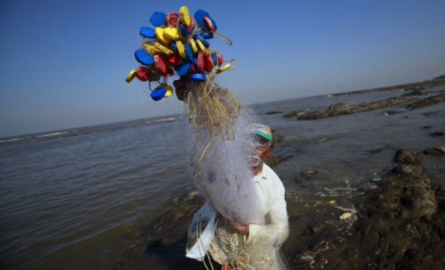 An Indian fisherman prepares his net before starting off for a day\'s catch in the Arabian sea...