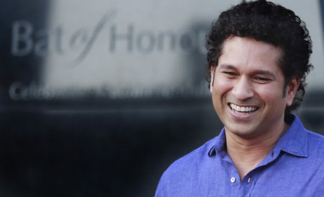 India\'s cricket icon Sachin Tendulkar smiles near a large steel bat which has been unveiled...