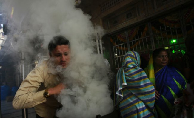 A Muslim devotee inhales incense smoke at the shrine of Sayed Haji Abdul Rehman Shah Baba Qadri...