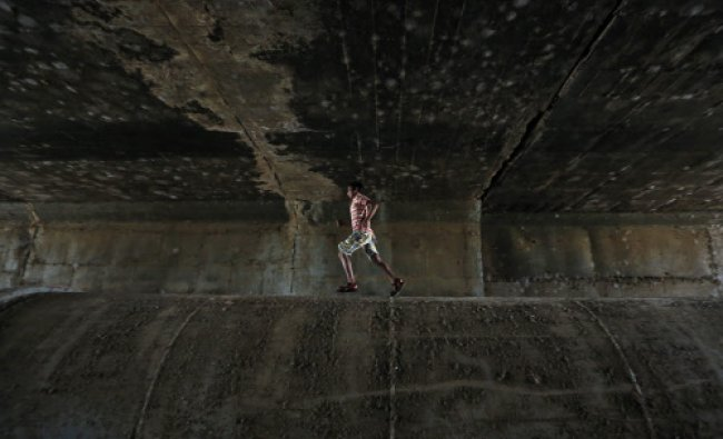 A boy runs on a water pipeline used as a pathway under a bridge in Mumbai...
