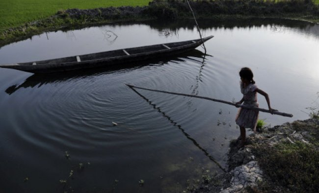 An Indian girl tries to pull a boat ashore near a paddy field in Mayong village...