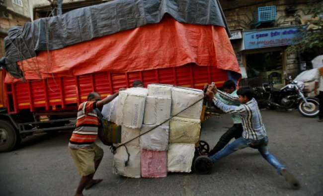 Indian laborers try to lift a turned cart loaded with sacks in Mumbai...