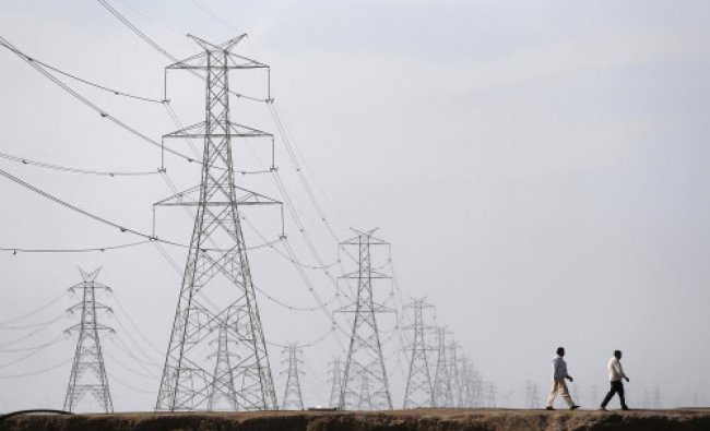 Men walk past electric pylons in Little Rann of Kutch in the western Indian state of Gujarat...