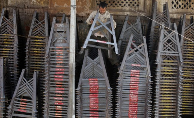 An Indian laborer arranges stands for fodder cutting machine at a market in Allahabad...