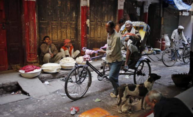 Indian people wait for customers while selling \'khoa\', or milk solid, as a rickshaw rides...