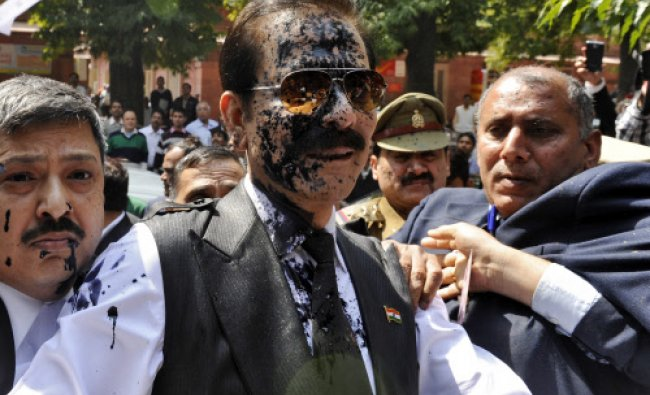 The Sahara group chairman Subrata Roy (C) with his face smeared in ink thrown by an unidentified ...