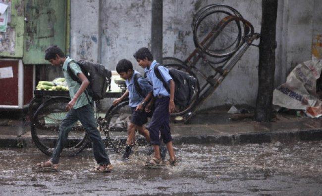 School children walk past a cucumber seller\'s push cart as it rains in Hyderabad...