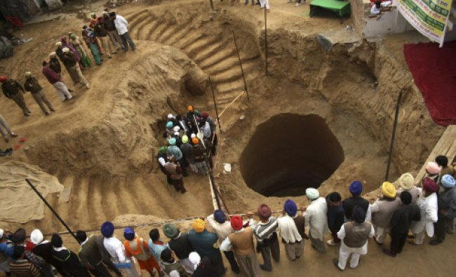 People gather at a site where remains of several people were unearthed from an un-used well...