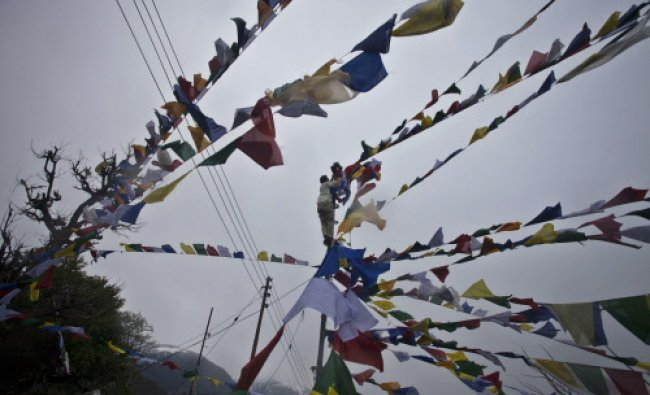 An exile Tibetan ties prayer flags called Lungta, or wind horse, on high poles...