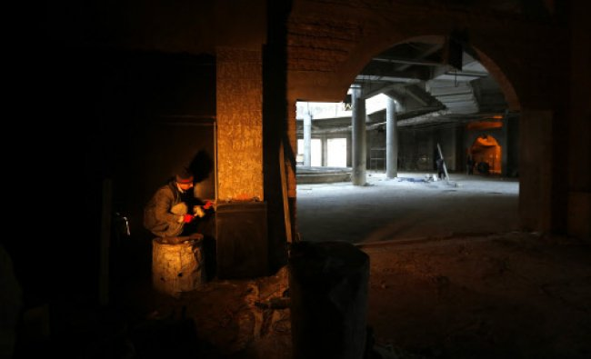An Afghan labourer works at a new parliament building being constructed by an Indian project...