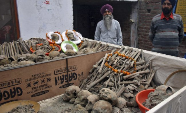 Men stand next to the remains of Indian soldiers retrieved from a well at a Gurudwara...