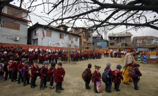 Schoolchildren stand in a queue outside their school in Srinagar...