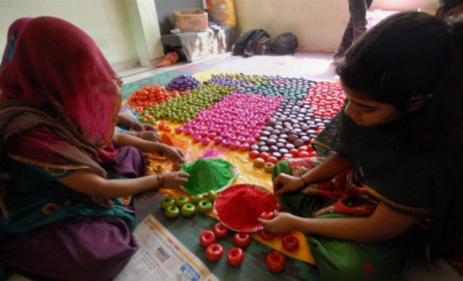 Women artisan give final shape and design to gulal gota made of lac, which contains...