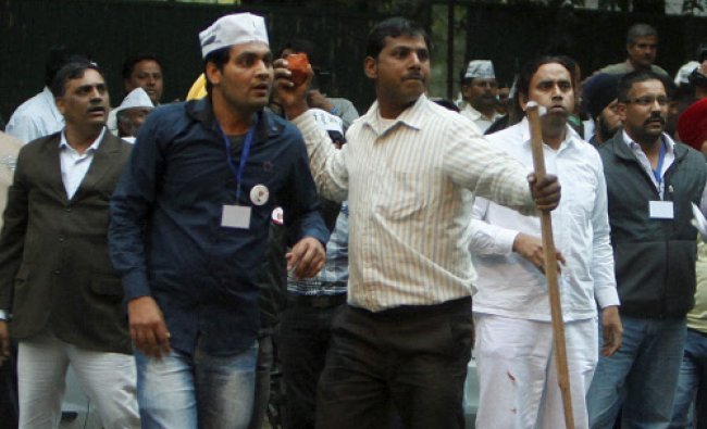 AAP supporters pet stones during a clash with BJP supporters outside BJP office...
