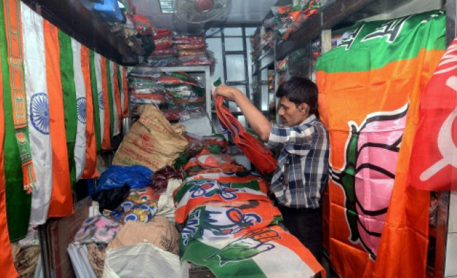 A shopkeeper arranging flags of various political parties for sale at his shop in Kolkata..