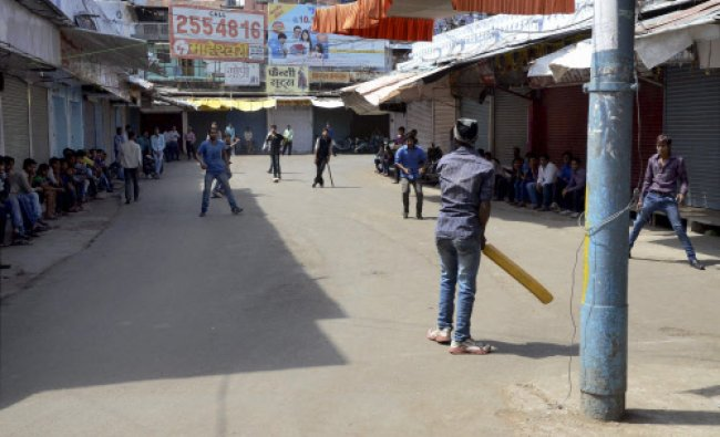 Shopkeepers playing cricket in front of their closed shops during \'Madhya Pradesh Bandh\'...